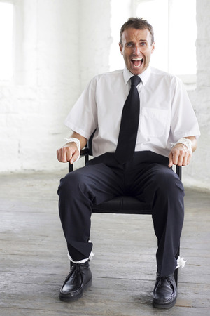 Tied up businessman screaming for help photo