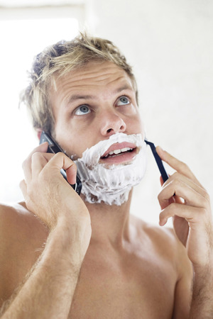Bare chested man shaving while talking on the mobile phone photo