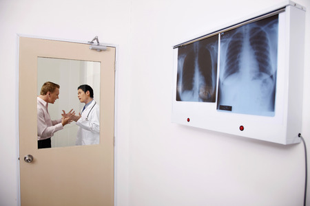 explains: Doctor revealing the bad news to patient, patient getting emotional Stock Photo