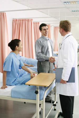 Man shaking doctor's hand, woman watching photo