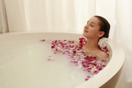 soaks: Woman relaxing in bathtub with flower petals Stock Photo
