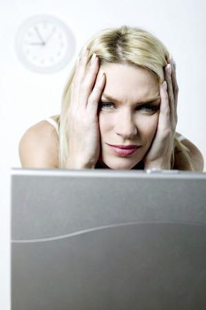 Frustrated woman using laptop photo