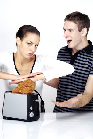 Man scolding his girlfriend for forcing dough into the toaster photo