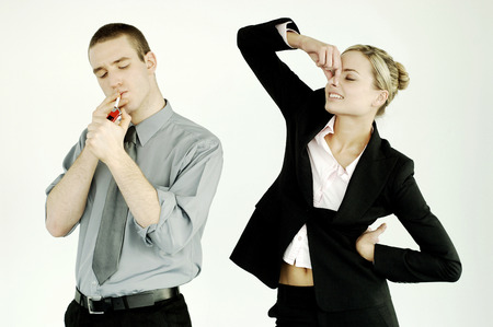 Businesswoman pinching her nose while businessman smoking photo