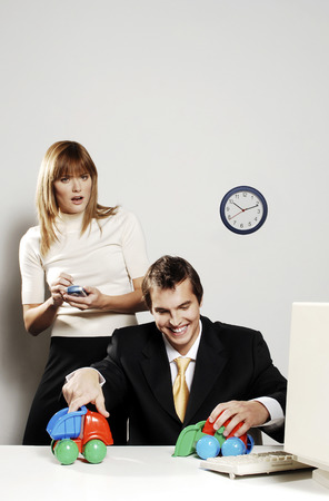 Businesswoman using palmtop while her colleague is playing with toy cars photo
