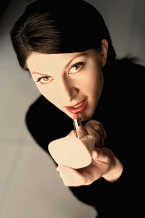 Businesswoman applying lipstick photo