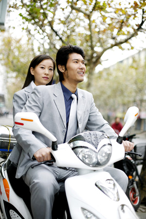 Businessman riding on a scooter with businesswoman sitting behind him photo