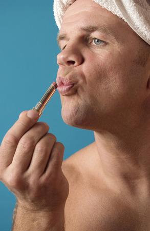 role reversal: Man applying lipstick on his lips
