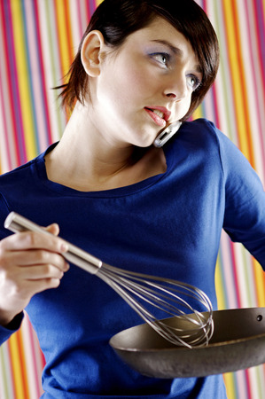 Woman talking on the phone while cooking photo