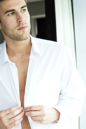 Man buttoning up his shirt photo