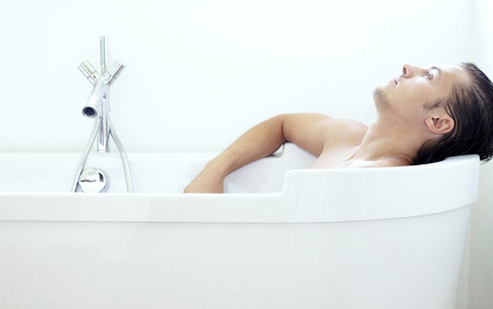 Man relaxing in the bathtub photo