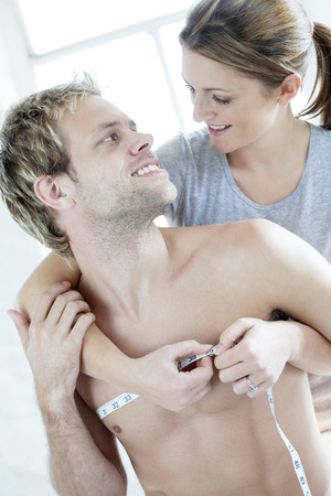 Woman measuring her husbands chest photo