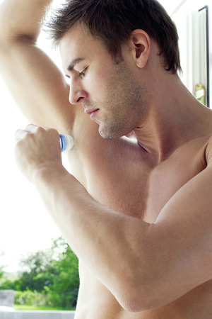 bare waist: Man applying deodorant on his underarm