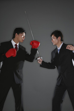 fencing foil: Businessman with boxing gloves challenging businessman with a fencing foil