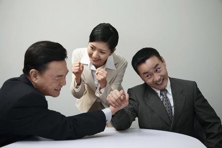 Businessmen arm wrestling with businesswoman cheering photo