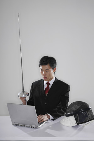 Businessman holding fencing foil while using the laptop photo