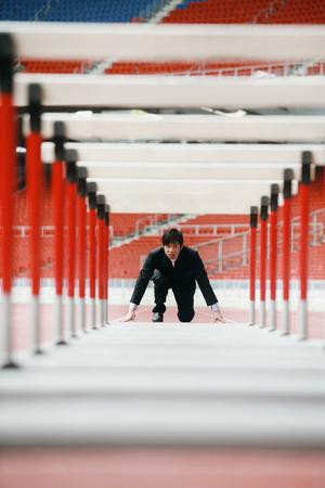 crouches: Businessman preparing to jump hurdles