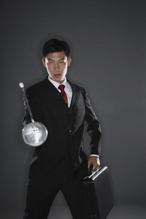 fencing foil: Businessman with a fencing foil
