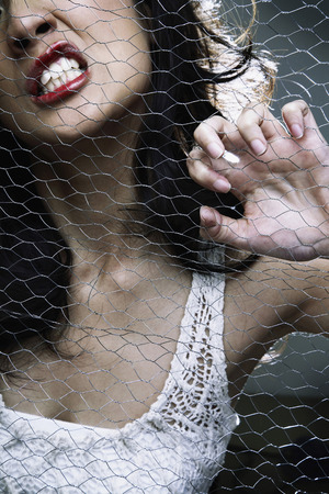 clenching teeth: Woman pulling on wire mesh while clenching teeth