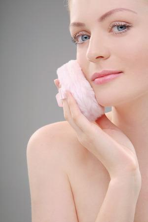 powder puff: Woman applying powder with powder puff