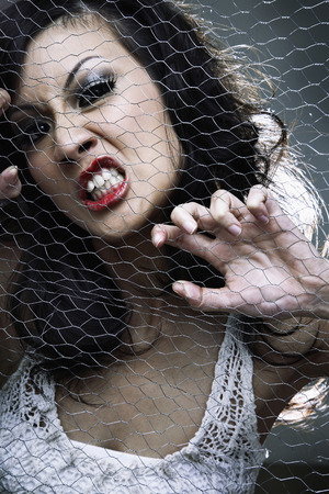 frowns: Young woman posing behind wire mesh