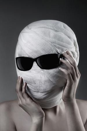 bandaged: Woman with bandaged face wearing sunglasses