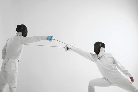 esgrima: Hombre en traje de esgrima atacar a su oponente Foto de archivo