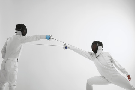 Man in fencing suit attacking his opponent photo