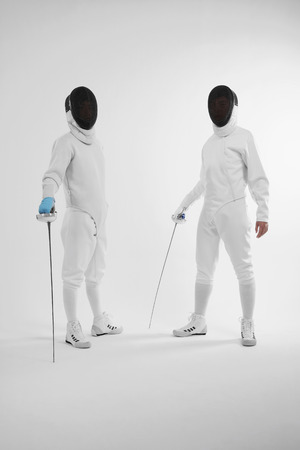 Two men in fencing suits looking at the camera photo
