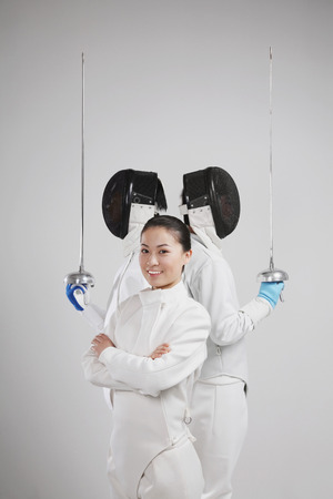 quarter foil: Woman and two men in fencing suits posing for the camera