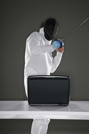 quarter foil: Man in fencing suit moving away from laptop Stock Photo
