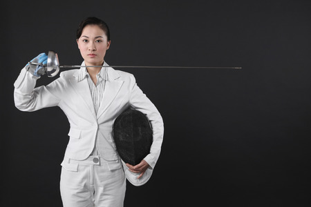 fencing foil: Businesswoman holding fencing mask and a fencing foil