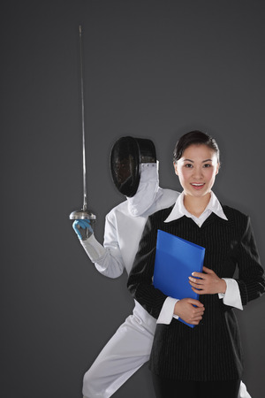 Businesswoman posing with a man in the background Stock Photo