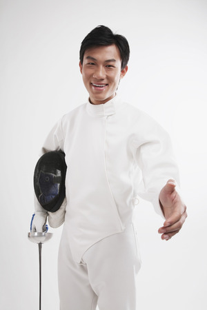 extending: Man in fencing suit extending hand for a handshake Stock Photo