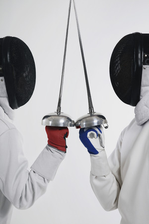 dueling: Two men in fencing suits in a duel