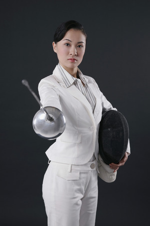 fencing foil: Businesswoman holding fencing mask and thrusting fencing foil