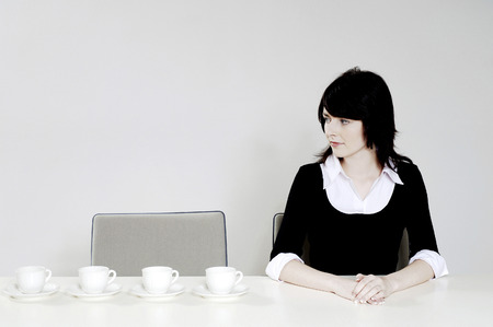 Businesswoman looking at an arrangement of coffee cups photo