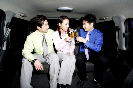 Business people drinking wine in the car photo