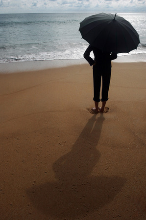 Businesswoman holding an umbrella on the beach photo