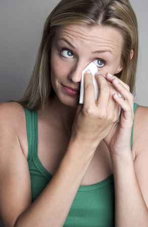 Woman wiping her tears with a tissue