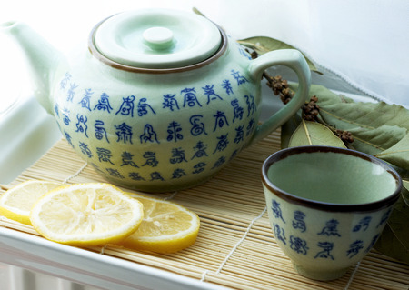 Teapot with tea cup and sliced lemons on a tray photo