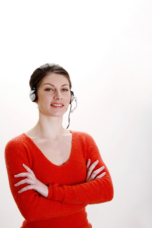 folding arms: Businesswoman folding her arms while talking on the headset Stock Photo