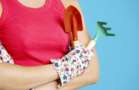 Woman holding trowel and garden fork Stock Photo