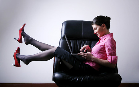 Businesswoman sitting on the chair playing with laptop photo