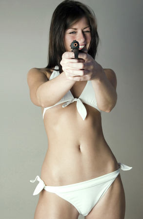 Woman in white lingerie pointing a gun at the camera photo