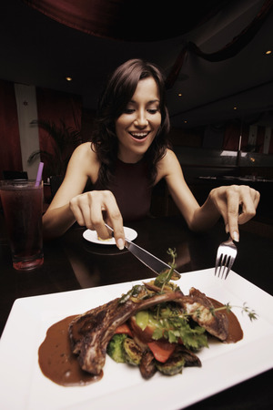 Woman tempted to eat lamb chop photo