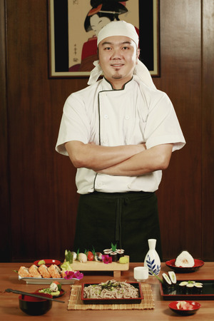 Chef standing in front of served food with his hands folded photo