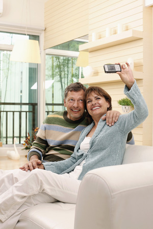 Man and woman taking picture with cell phone photo