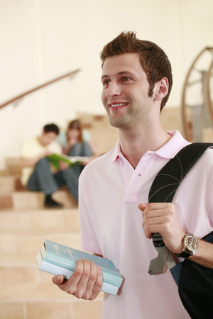 Man carrying backpack while two people are having discussion in the background