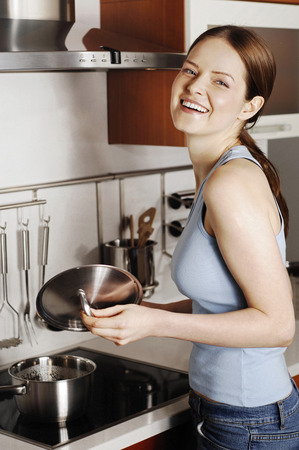 Woman laughing while cooking in the kitchen photo